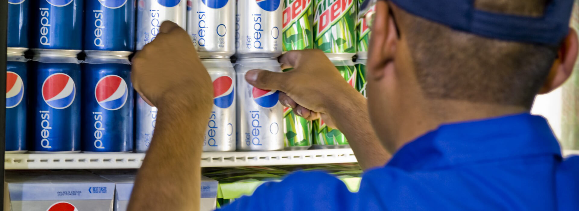 Worker loading cans of Pepsi into a refrigerator.