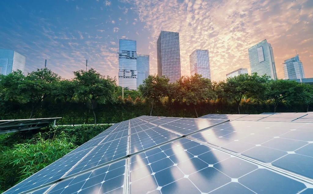 Image of solar panels with high-rise office buildings in the background.