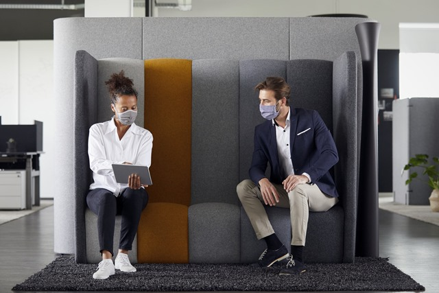 Two people wearing masks in an office setting.