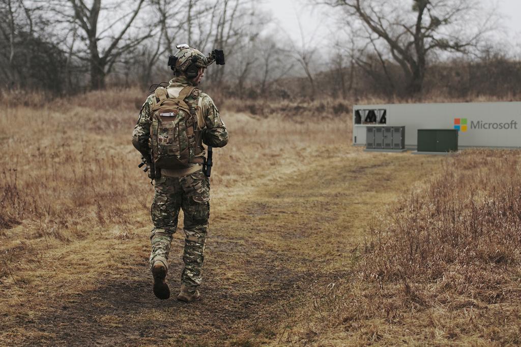 木々に覆われた野外の遠隔地にある Microsoft Modular Datacenter へ向かって歩いている人物