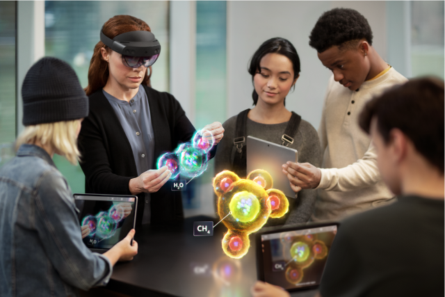 Instructor wearing a HoloLens, holding and visualizing a holographic H2O molecule. Four students visualizing that molecule and a holographic CH4 molecule through three mobile tablets.