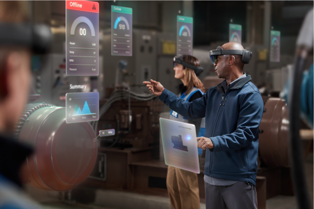 "A man wearing a HoloLens in a factory visualizes and points to holographic data surrounding a factory engine, signaling the machine is ""offline."""