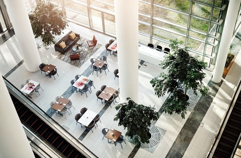 View from an internal balcony inside a high-rise, smart building using Azure IoT looking down on a light-filled lobby filled with tables, chairs, and plants.